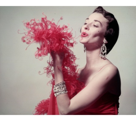 Model blowing on red feather boa & wearing large rhinestone earrings & bradelets for article featuring the little red dress 1950