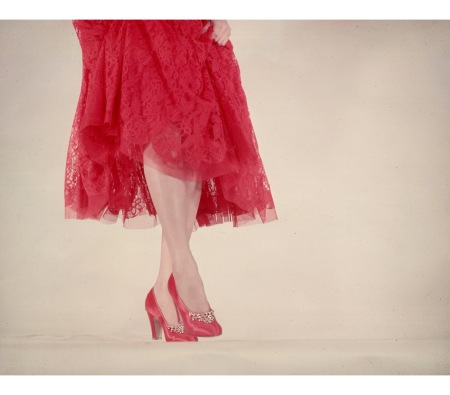 Model wearing rhinestone-trimmed red satin pumps & red lace skirt for article featuring the little red dress. 1950