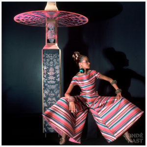 Horst P. Horst captures legendary model Veruschka in this photograph, which appeared the November 15, 1966, Vogue. She wears whirligig striped evening pajamas by Arnold Scaasi, which, at the time, were an exceptionally stylish and progressive alternative to traditional evening gowns. She's seated next to a sculpture by Marisol, which works nicely with the colors she wears and the shape she creates with her stated stance. The shadows of both subjects against a green wall make this particularly exotic and borderline mysterious. Condè Nast Archive