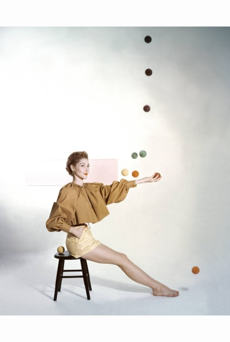 model-seated-on-stool-juggling-brightly-colored-tennis-balls-wearing-carolyn-schnurers-comet-yellow-collection-john-rawlings-vogue-january-1953-copia