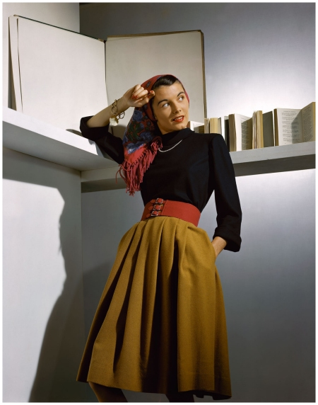 A Vogue model photographed in a camel-coloured wool skirt accessorised with a wide red belt, a fringed scarf and pearls, 1941 Horst P.Horst B