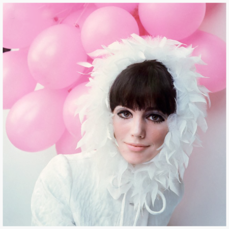 Photo David Mccabe -  Model Susan Bottomly shows off The London Look with makeup by Yardley, wearing a halo of coq feathers on a white satin cap, by Madcaps. Behind her is a bundle of pink balloons. Circa December 1965