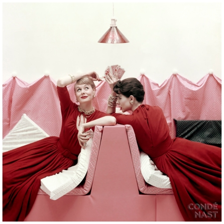 """Models Sitting in Booth in Red Jersey Dresses""Original caption: Two seated models in red, one wearing dress of wool-and-silk jersey with drawstring neckline and push-up sleeves, other wearing dress of similar style in jersey of wool and rayon. Condé Nast Archive/Corbis"