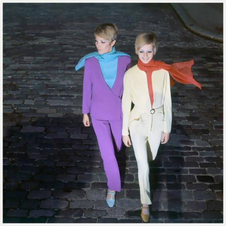 Two English models, Sara Crichton-Stuart and Twiggy, walk down a cobblestone street, wearing pantsuits by Simon Massey - Sara Crichton-Stuart and Twiggy - Photo Ray Traeger 1966