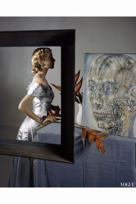 A model in profile illustrates three points of beauty. She poses before Pavel Tchelitchew's painting 'The Head of Gold.' vogue-september-1947