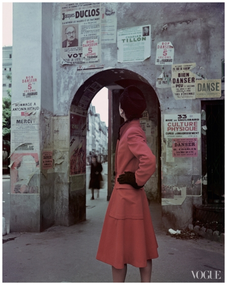 Model standing in front of an archway in Paris wearing a red coat with oversize pockets by Molyneux, black gloves, and a hat Photographed by John Rawlings, Vogue, March 1946