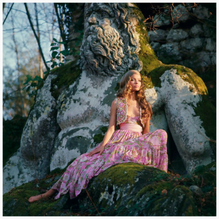 Model Veruschka sitting on the Baroque sculpture of a man in the , wearing pink floral gypsy dress with a sash at the waist and a little beaded bolero, by Ken Scott; Hair by Alba e Francesca. Circa April 1969 Franco Rubartelli