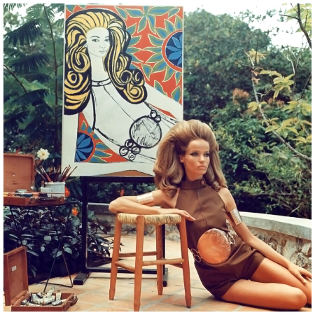 Veruschka is posing for artist Genaro de Carvalho who paints a colorful, graphic portrait of her, as she is wearing a brown split leg halter one piece, by Ginori, with big, round, copper buckle and bracelet - anklet bands by Sant'Angelo