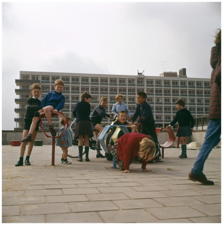 A group of children playing on modern objects on a playground with a building in the background, 1969