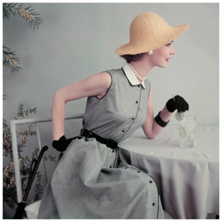 Frances Mclaughlin-Gill Model in black and white gingham dress with pique collar, gloves and straw hat, sipping an ice cold drink garnished with limes 1952