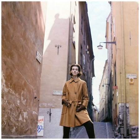 Judy Dent in amber coat of thick rainproof cotton lined with brushed wool from Hettemarks of Sweden, photo by Vernier in cobbled alleys of Stockholm, Sweden, Vogue, Oct. 1962