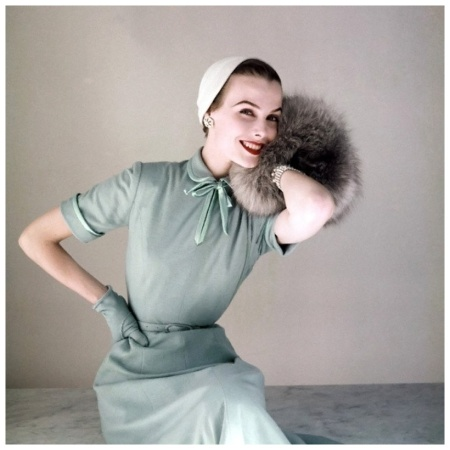 Model in Heller baby blue worsted jersey dress with satin bow at neck by Richard Cole, little felt hat by Amy and Norwegian blue fox muff by Annis Furs, 1952 Photo by John Rawlings