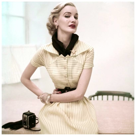 Photo Frances McLaughlin-Gill Model in a yellow and black pinstriped dress sits beside a medium-format camera. Circa June 1952