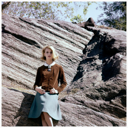 Photo Sante Florano - Woman leaning against rock - Model in creme de coco cardigan jacket of Catoni velveteen, long-sleeved Irish linen blouse, Clear Sandringham blue flared skirt of Warren of Stafford wool loomed in America. All by Robert Sloan 1962
