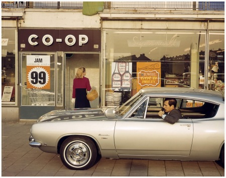 Pipe Smoking man in a car (Plymouth Barracuda) waiting for woman shopping in a co-op supermarket, 1969