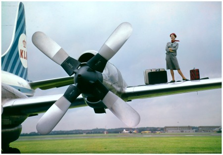 Singer Chunks Corry posa con valigie accanto l'elica sull'ala di un aereo KLM, Paesi Bassi, circa 1960