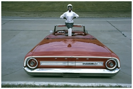 A woman donning racing goggles, crash helmet, grey skirt and white boots poses with a 1964 Ford Galaxie 500 XL convertible along a raceway Photo Gene Laurents