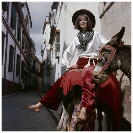 Model riding a donkey in Spain wearing claret velvet trousers with wide legs, a white satin gypsy blouse with gathered voluminous sleeves, both by Anne Klein; a printed scarf and a burgundy Goucho felt hat by Cerruti 1969 Photo Henry Clarke