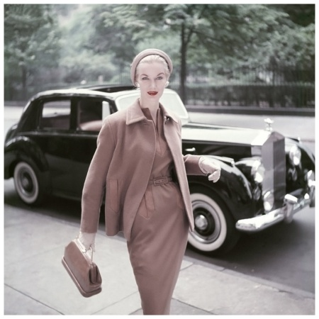 Model wearing Digby Morton's camel's hair-and-wool suit with a felt cloche by Knox, Milch leather bag, walnut earrings by Coro, and Yardley 'Vivid' lipstick pictured in front of a Rolls-Royce 1953 Clifford Coffin