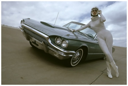 Posed with 1964 Thunderbird in eyeshadow blue, model wearing leotard of silvery white stretch fabric with a wide chained turtleneck and long sleeves. Worn with space-queen helmet and white leather boots 1964 Photo Gene Laurents