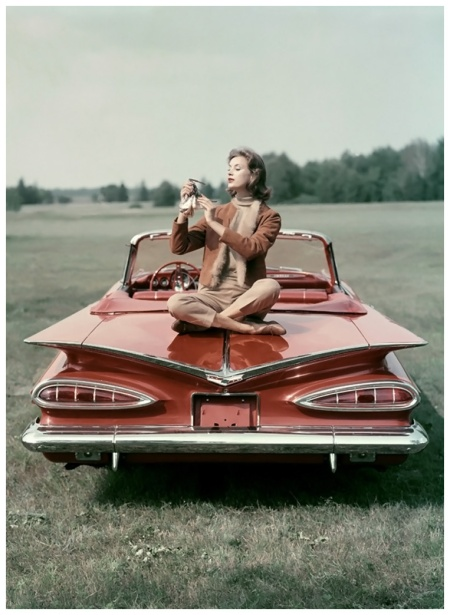 Seated on the wing-back of a red 1959 Chevrolet Impala Convertible, model wearing a suede cardigan lined in guanaco, over a caramel wool turtleneck and pants Photo John Rawlings 1958