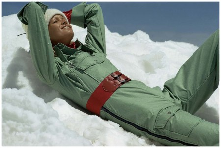 Model reclined in the snow wears green ski overalls by Liberty Bell with a red belt at waist Photo Mike Reinhardt 1972