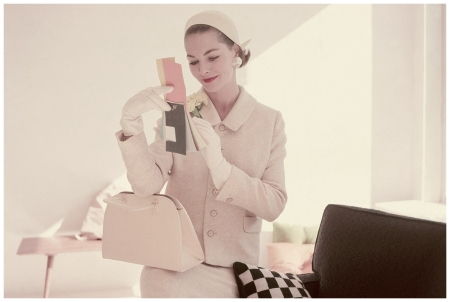 Model sitting on arm of sofa wearing chamois yellow suit by Faye Wagner with felt helmet by Miss Ruth, linen-textured bag by Greta Photo Leombruno-Bodi 1955