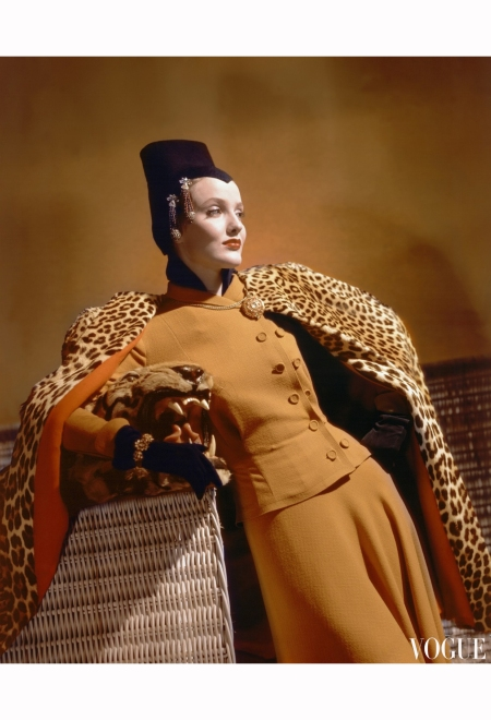 Model wearing golden wool dress, gold jewelry, brown jersey hat, and leopard cape, leaning on basket horst-p-horst-vogue-august-1940