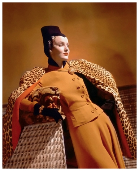 Model wearing golden wool dress, gold jewelry, brown jersey hat, and leopard cape, leaning on basket Photo Horst P. Horst Condé Nast Archive 1940 corbis
