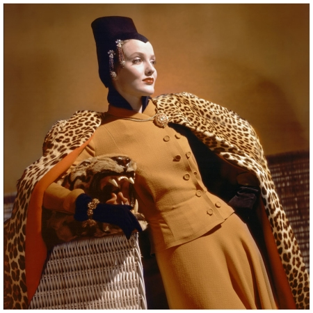 P Model wearing golden wool dress, gold jewelry, brown jersey hat, and leopard cape, leaning on basket Photo Horst P. Horst Condé Nast Archive 1940
