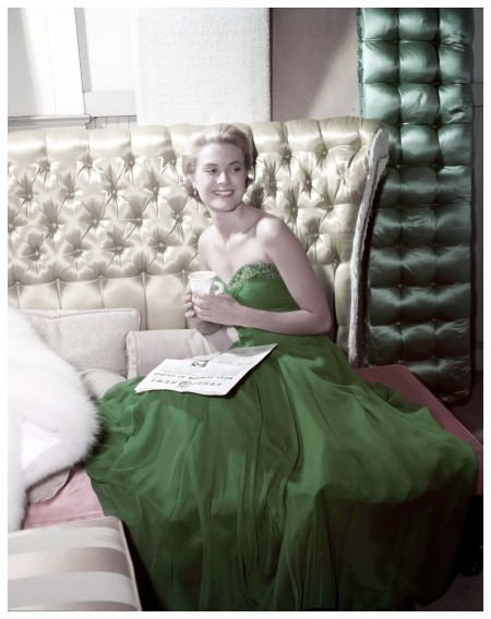 Grace Kelly wearing a green dress for St Patrick's Day, 1954. She is reading a copy of MGM's Studio News Photo Gene Lester