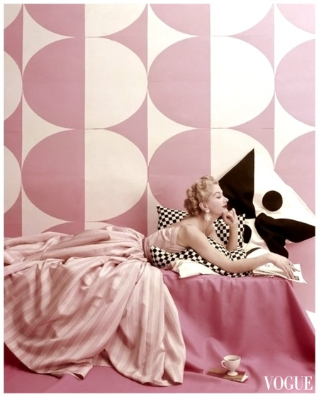 Model lounging on bed, wearing Claire McCardell's pink and white striped dress Vogue 1952 Richard Rutledge