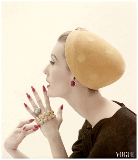 model Mary Jane Russell's head wearing hat of lemon velour by Adolfo of Emme, holding gold and diamond jewels from David Webb Photo Richard Rutledge Vogue Sept 1955