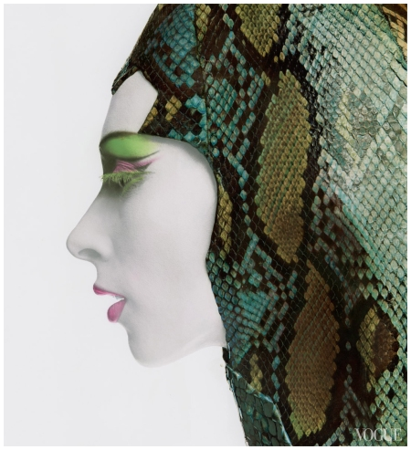 Close-up of model in profile, wearing white foundation makeup, green upside-down false eyelashes, and purple and green eye shadow, mauve lipstick and multicolored snakeskin hood by Adolfo Photo Bert Stern, Vogue, November 1965