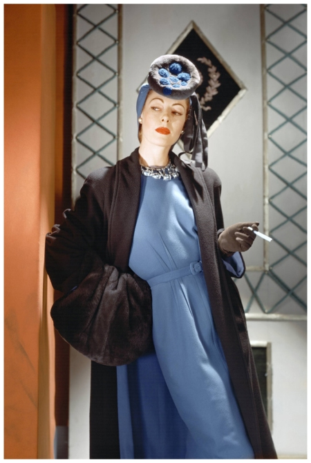Standing model with cigarette, wearing brown wool coat, blue wool dress, nutria hat, and huge nutria muff Horst P. Horst 1941
