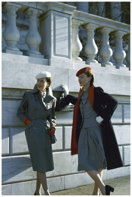 Two models by a building, one wearing a gray wool flannel trench coat, the other wearing a navy blue reefer coat of wool chinchilla, its reverse faced in red and a soft, checked wool suit Vogue 1943 John Rawlings
