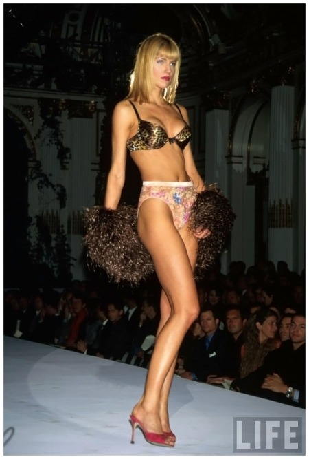 Model Tricia Helfer wearing leopard print bra and flowered underpants on fashion show runway for Victoria's Secret 1998