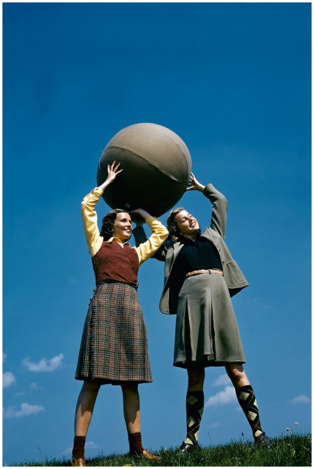 Two models holding large ball aloft, one wearing wool shirt, red jerkin, and tweed kilt, and one wearing long jacket, knee socks, and wool skirt, August 1940 Photo Toni Frissell copia