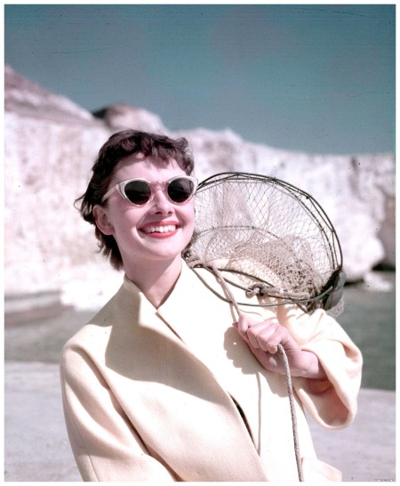 1951. A portrait of US Film star Audrey Hepburn pictured on the beach whilst carrying a net.
