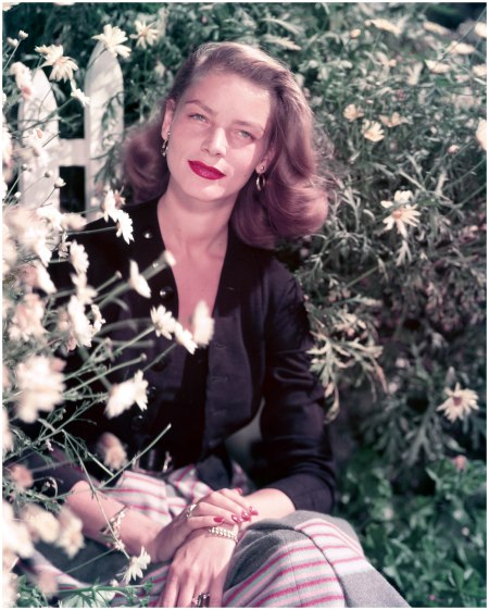 Lauren Bacall, US actress, wearing a black jacket and top with a skirt with horizontal stripes, posing in a garden beside a display of daisies, circa 1950. (Photo by Silver Screen Collection:Getty Images