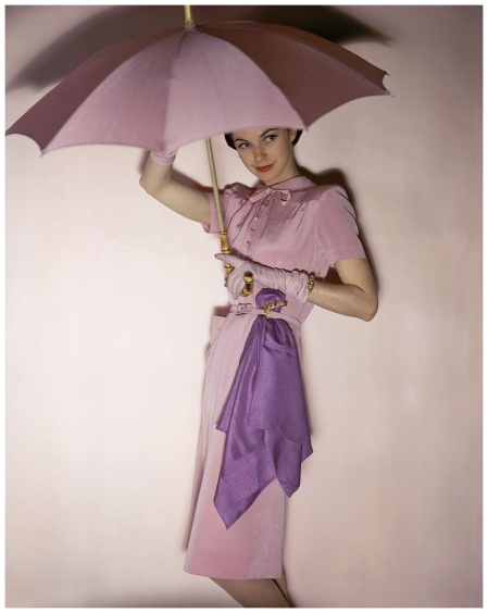 Model holding pink parasol wearing Traina-Norell's pink belted, button top rayon and wool,1944 Photo John Rawlings Fairchild Archive
