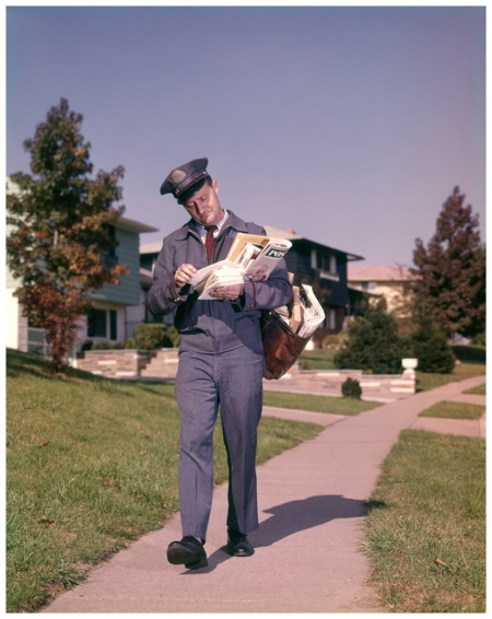 1960s Postman Delivering Mail Suburban Neighborhood Sorting Letters Walking On Sidewalk 1964 Photo H. Armstrong Roberts