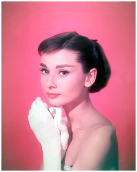 Audrey Hepburn 1957 wearing a strapless dress, holding her white-gloved hands near to her face. (Photo by Hulton Archive:Getty Images)
