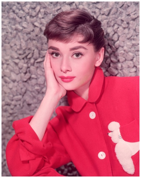 Audrey Hepburn, leaning on her hand in a red jacket with a poodle applique. (Photo  Bud Fraker Hulton Archive:Getty Images)