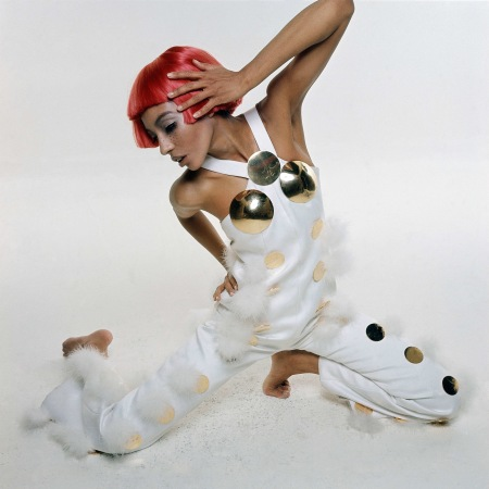 Model wearing a Courreges bunny jumpsuit in white sateen, with white pompons, big brass polka dots and breast cups, and a red Dutch boy wig Photo bert Stern 1969