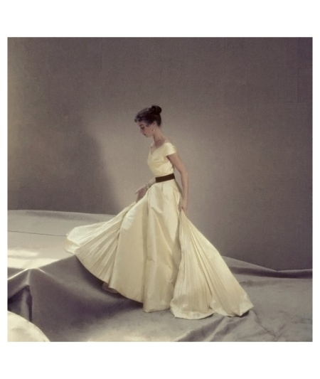 Model wearing apple green satin evening dress by Griffe with pleats shooting out at either side. Circa October 1951 Photo Henry Clarke