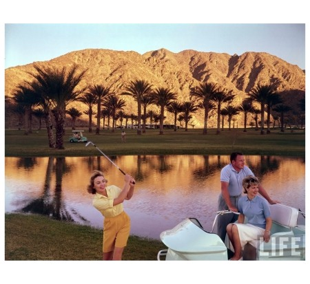 Golfer swinging in front of pond with Joan Bohannon and husband standing nearby Palm Springs, CA, US 1961 Photo Ralph Crane b