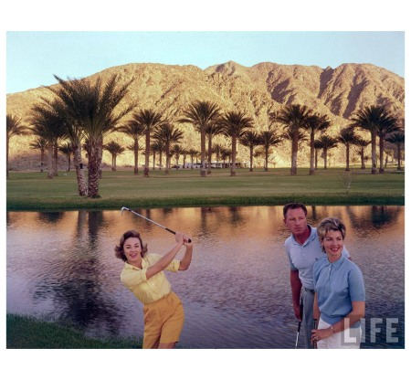 Golfer swinging in front of pond with Joan Bohannon and husband standing nearby Palm Springs, CA, US 1961 Photo Ralph Crane