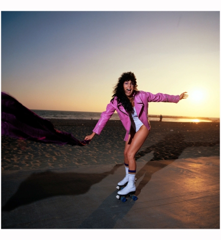 Cher, 1979 roller skates at Venice Beach wearing a pink leather jacket and white swimsuit Photo Douglas Kirkland