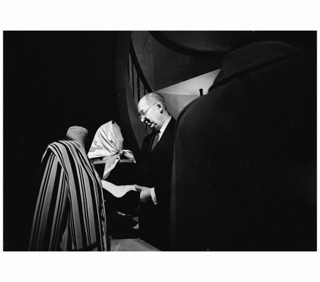 Fashion designer Jacques Heim (1899 - 1967) in his workshop, examines a jacket and a headscarf 1965 Photo Reg Lancaster